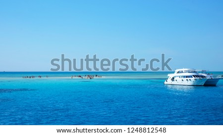 Landscape of the Red Sea. White yachts await tourists in the azure water of the Red sea, near a tiny white sandy island. Egypt, Sharm El Sheikh. #1248812548