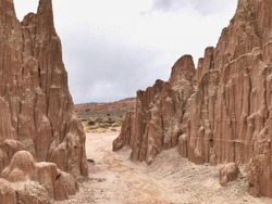 Landscape of trail between large tan and brown vertical rock formations or hoodoos in Cathedral Gorge State Park in Nevada