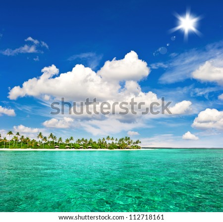 landscape of tropical island beach with palm trees and sunny blue sky