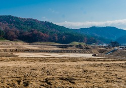 Landscape of vacant land at construction site with tree covered mountain and blue sky in background.