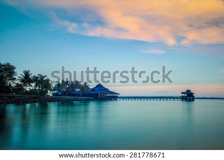 Landscape of water house on stilts, pontoon and palm trees at sunset in Indonesia