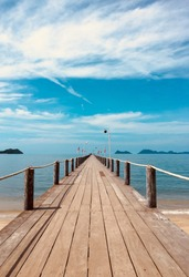 Landscape of wooden bridge in blue sea on tropical beachand blue sky background .