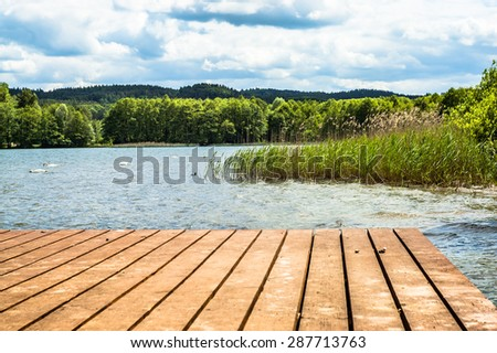 Landscape of wooden pier over beautiful lake in the summer. Vacation and holiday time, nature composition or postcard. #287713763