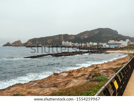 Landscape of Yehliu Geopark, a cape on the north coast of Taiwan. A landscape of honeycomb and mushroom rocks eroded by the sea with city buildings in background. #1554259967
