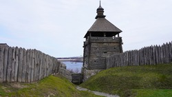 Landscape on a fortress in Europe, a wooden structure fenced with a palisade, a tower against the background of the sky and the river. Thick beams with a sharp top.