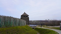 Landscape on a historic temple made of wood in Europe. The fortress is fenced with a wooden palisade against the background of the sky and the river. Thick beams with a sharp top.