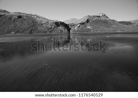 Landscape on the beaach with the reflection in the water.  Taken at Karioitahi beach in New Zealand.  Black and white.