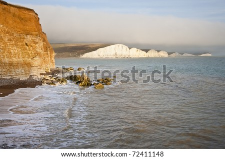Landscape overlooking cliff tops to white cliffs in distance with waves rolling in