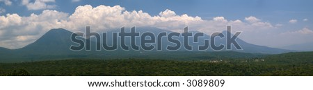 Landscape panorama showing three El Salvador volcanoes and the village of Juayua.