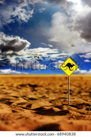 Landscape photo of a kangaroo warning yellow sign in the Australian outback with dramatic sky and red earth