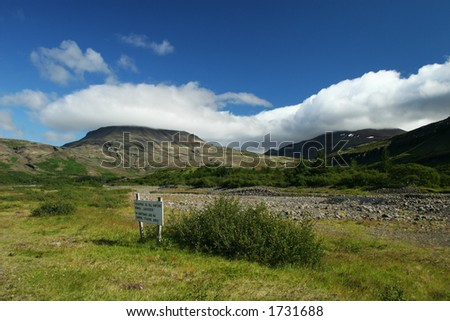 Landscape photo of a valley in a clear weather, sign on ground says, no camping, fishing area