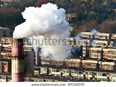 Landscape photo of chimney, smoke and air pollution in resident block