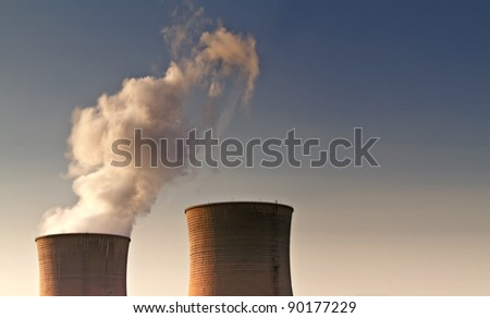 Landscape photo of giant power supply chimneys smoking in the sky