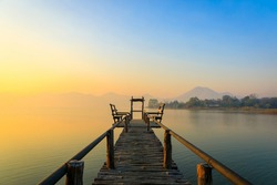 Landscape photo of Lake and mountain on the background with a little white fog sunshine light on the morning. and wooden bridge with seat for sit.