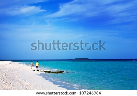 Landscape photo of  Romantic happy senior man and woman couple walking on a tropical beach with bright clear blue sky