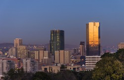 Landscape photo of the city of Pretoria in South Africa at sunrise with sun reflecting on the reserve back.