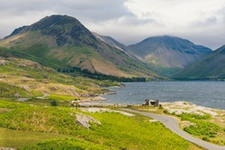Landscape photo of Wast Water in the Lake District Natinal Park with Great Gable Moutain in the background and the winding country road over the fells leading to Great Gable.