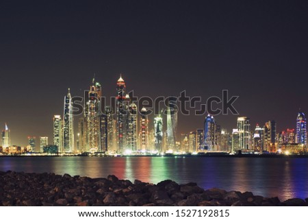Landscape photo of water, stones and modern skyscrapers in Dubai Marina