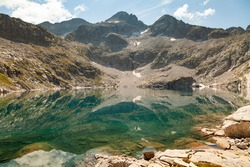 Landscape photograph of a lake with clean and turquoise waters that reflect the silent silhouettes of the mountains in summer, Aragonese Pyrenees, Huesca province, Posets-Maladeta Natural Park.