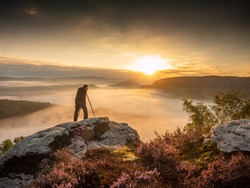 Landscape photographer in action taking picture. Silhouette man photographing against misty landscape and morning sky. Autumn colorful sunset