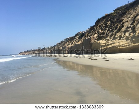 Landscape pic of Solana beach with ocean on left and cliffs on right during daytime with clear blue/white sky.
