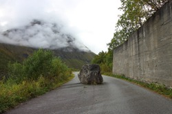 Landscape picture of a large stone blocking the road in Norway