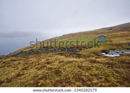 Landscape Picture of countryside in Faroe islands shown sheep grazing or pasture land in moorland on top of hill in fjord, wired fences, wild creek with water cascade during typical spring rainy day.