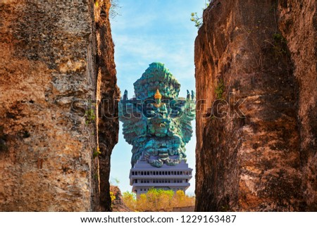 Landscape picture of old Garuda Wisnu Kencana GWK statue as  Bali landmark with blue sky as a background. Balinese traditional symbol of hindu religion. Popular travel destinations in Indonesia. #1229163487