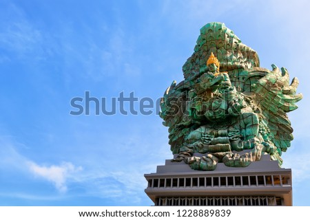 Landscape picture of tallest Garuda Wisnu Kencana GWK statue as  Bali landmark with blue sky as a background. Balinese traditional symbol of hindu religion. Popular travel destinations in Indonesia. #1228889839