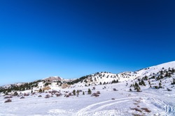 Landscape picture showing a Aroania (Chelmos) mountains area covered with snow near Kalavrita, Greece with blue sky for background. Winter landscape. Winter scene. Snowfall in mountains. Snowy winter