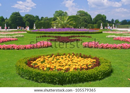 Landscape picture with bright flowers on the background of statues, Vienna, Austria.