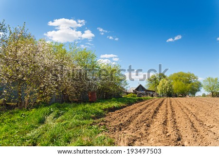 landscape plowed field on a background of rural houses