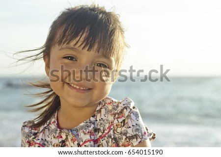 Landscape portrait of hispanic 4 year old girl sitting at the beach is looking at the camera smiling. Taken at Playa del Carmen, Mexico.