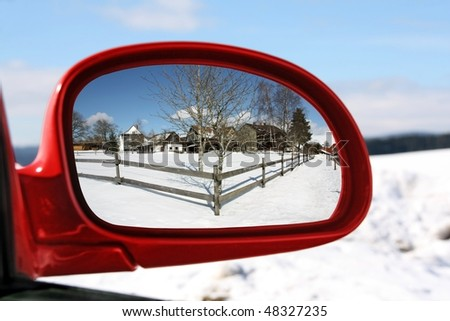Landscape reflected in the rear view mirror of a red car
