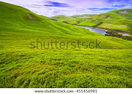 Landscape scenery of green valley, hill, river and cloudy blue sky. Pentland hills, Scotland #451456981
