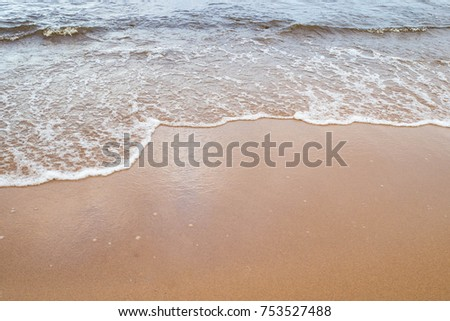 Landscape Sea waves rolling and lapping on the sandy shore. Elements of natural water. Ocean surf waves. Storm wild sea - dangerous weather.   #753527488
