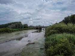 Landscape shot of a river with a bridge whose pillars reflect in the water with a cloudy sky