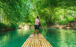 Landscape shot of man (tourist) rowing bamboo raft, whilst on cruise on vacation in Montego Bay, Jamaica, Caribbean. Martha Brae 2019.