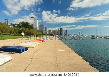 Landscape skyline view of the Lakefront trail in Grant Park along Lake Michigan in Chicago with a polarized blue sky and a jogger exercising.