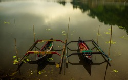 Landscape. Traditional boats on the lake. Rainy, cloudy and foggy weather. Water reflection. Nature background. Environment concept. Bratan lake, Bedugul, Bali, Indonesia