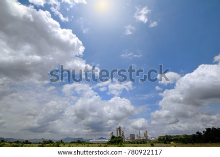 Landscape view,Factories in the middle of the pasture ,The back there are mountains in the overcast sky and  beautiful cloudy with the sun shining force.