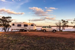 Landscape view of a a large white caravan and modern 4WD vehicle at a free camp next to the nearly dry salt Lake Norring near Wagin in Western Australia in late afternoon sunshine.