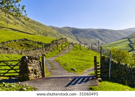 Landscape view of a gate and cattle grid on the path from Hartsop to Hayeswater in the English Lake District National Park in Cumbria, England, United Kingdom.