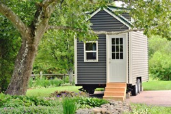 Landscape view of a tiny gray eco friendly house on wheels