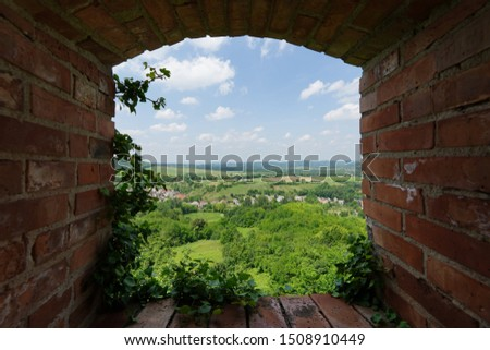 Landscape view of a village from a window of a castle ruin. Picture in picture, the scenery is framed by red bricks