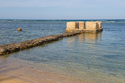 Landscape view of abandoned empty tropical beach at coastal seaside resort town in egypt africa with old roman remains of harbour