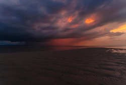Landscape view of beach, sea at tide and silhouette dark dramatic sunset sky and clouds in the evening. Phuket. Thailand