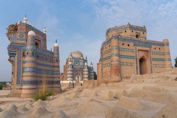 Landscape view of beautiful ancient medieval islamic architecture with tomb of Bibi Jawindi in middle and traditional graveyard in foreground in Uch Sharif, Bahawalpur, Punjab, Pakistan