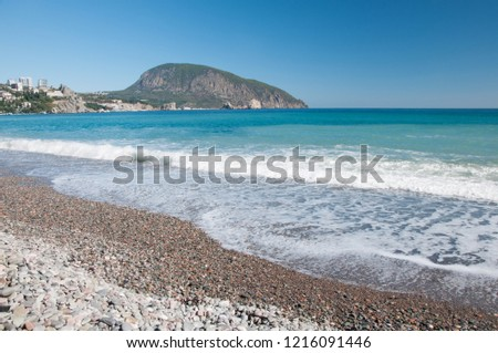Landscape view of Black Sea coastline with pebble beach and Ayu-Dag mountain in the background, Gurzuf resort, Crimea, Russia