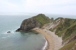 Landscape view of cliffs in Dorset by a sandy beach. The cliffs are covered in grass